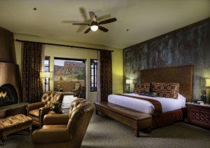 Et av soverommene til Gateway Canyon Resort, med king size seng og peis med 2 stoler ved siden av